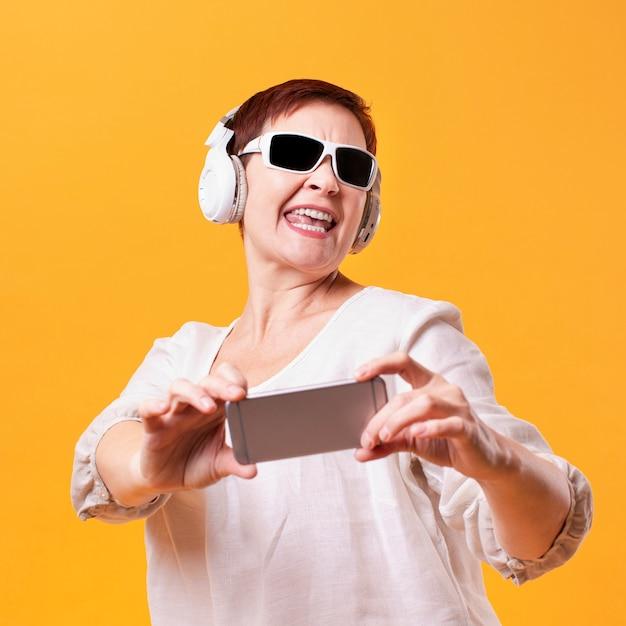Szczęśliwa kobieta z hełmofonami i telefonu egzaminem próbnym Darmowe Zdjęcia