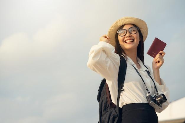 Szczęśliwa Kobieta Z Kamerą I Paszportowym Czekaniem Dla Podróży Samolotem. Premium Zdjęcia