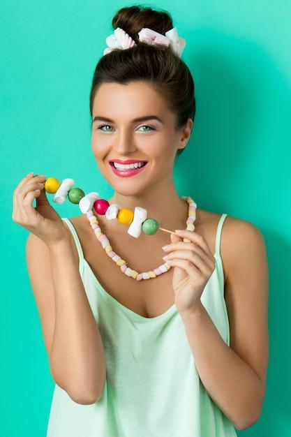 Szczęśliwa Kobieta Z Kolorowy Makijaż I Słodkie Cukierki Na Szpikulec Premium Zdjęcia