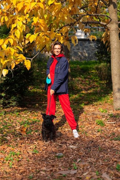 Szczęśliwa Kobieta Z Psem W Parku Z Jesiennych Liści Darmowe Zdjęcia