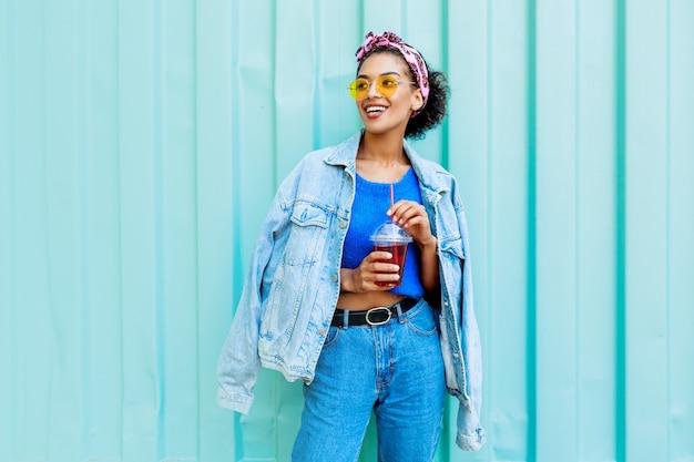 Szczęśliwa Kobieta Ze Stylowymi Włosami Pozowanie Na świeżym Powietrzu, Trzymając Wiśniową Lemoniadę, Ubrana W Dżinsową Kurtkę I Niebieski Wełniany Sweter. Darmowe Zdjęcia