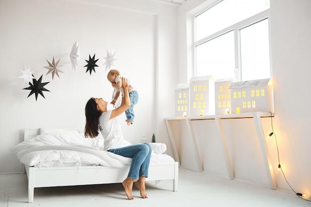 Szczęśliwa kochająca rodzina. matka bawi się z dziećmi w sypialni Premium Zdjęcia
