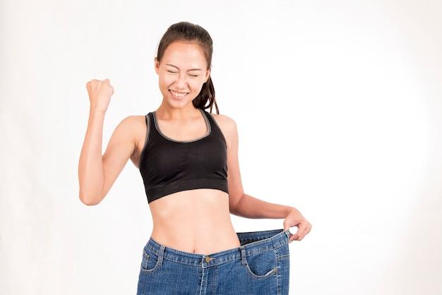 Szczęśliwa ładna kobieta gubił ciężar szczupły kształt z dużymi cajgami na białym tle. Premium Zdjęcia