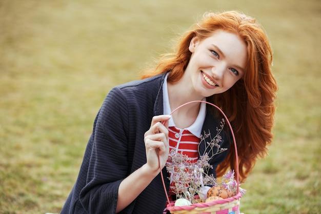 Szczęśliwa ładna Kobieta Trzyma Pyknicznego Kosz Z Easter Jajkami Outdoors Darmowe Zdjęcia