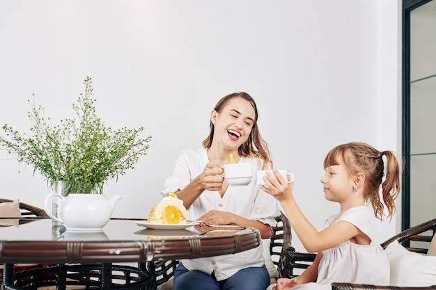 Szczęśliwa ładna Młoda Kobieta Picia Herbaty I Jedzenia Domowej Roboty Herbatniki Z Małą Córeczką Premium Zdjęcia