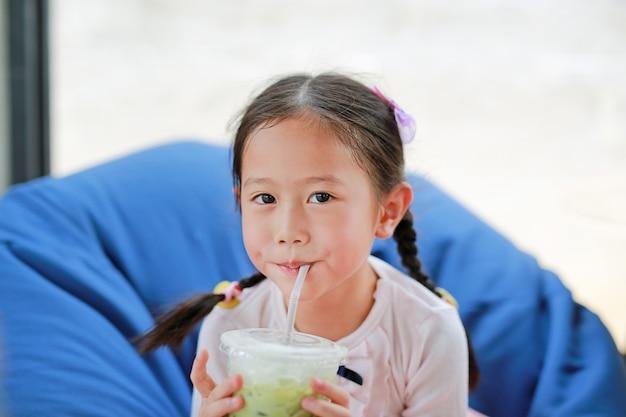 Szczęśliwa mała azjatycka dziecko dziewczyna pije lukrową matcha zielonej herbaty lying on the beach na kanapie przy kawiarnią. Premium Zdjęcia