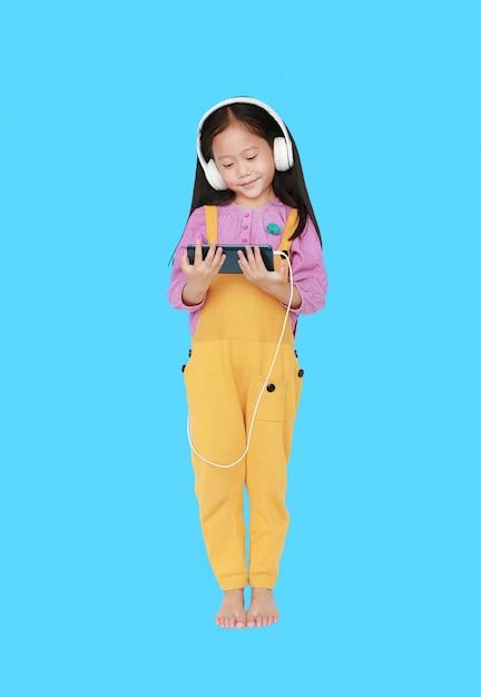 Szczęśliwa Mała Azjatycka Dziecko Dziewczyna W Różowożółtych Ogrodniczkach Z Hełmofonami Cieszy Się Słuchającą Muzykę Premium Zdjęcia