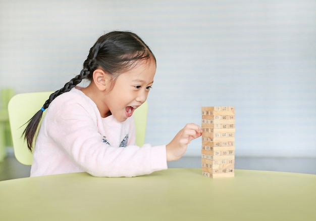 Szczęśliwa Mała Azjatycka Dziecko Dziewczynka Grająca W Drewniane Klocki Wieża Dla Umiejętności Mózgu I Rozwoju Fizycznego W Klasie. Skoncentruj Się Na Twarzy Dzieci. Koncepcja Wyobraźni I Uczenia Się Dzieci. Premium Zdjęcia