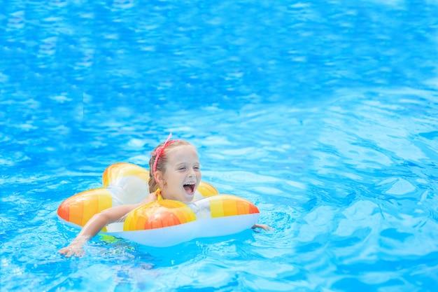 Szczęśliwa Mała Dziewczynka Bawić Się Z Kolorowym Nadmuchiwanym Pierścionkiem W Plenerowym Pływackim Basenie W Gorącym Letnim Dniu. Dzieci Uczą Się Pływać. Zabawki Wodne Dla Dzieci. Dzieci Bawią Się W Tropikalnym Kurorcie. Rodzinne Wakacje Na Plaży. Premium Zdjęcia