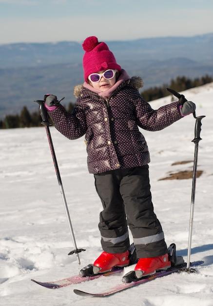 Szczęśliwa mała dziewczynka na nartach zjazdowych Premium Zdjęcia