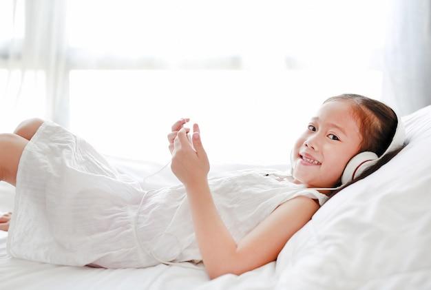 Szczęśliwa Mała Dziewczynka Używa Hełmofony Słucha Muzykę Smartphone Podczas Gdy Kłamający Na łóżku W Domu. Premium Zdjęcia