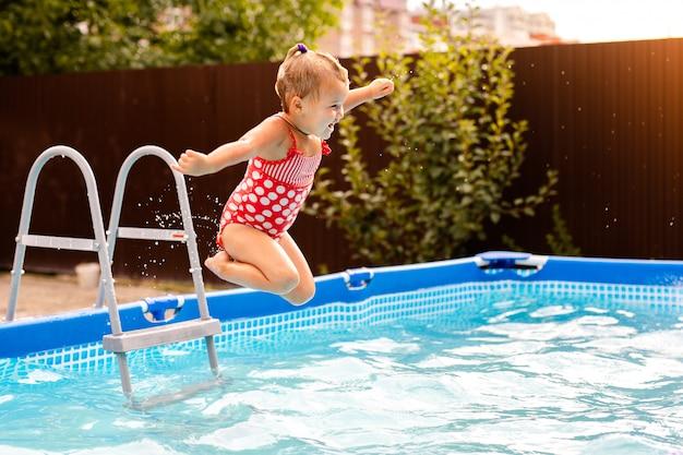 Szczęśliwa Mała Dziewczynka W Czerwonym Swimsuit Doskakiwaniu W Plenerowego Pływackiego Basen W Domu. Dziewczynka Uczy Się Pływać. Wodna Zabawa Dla Dzieci. Premium Zdjęcia