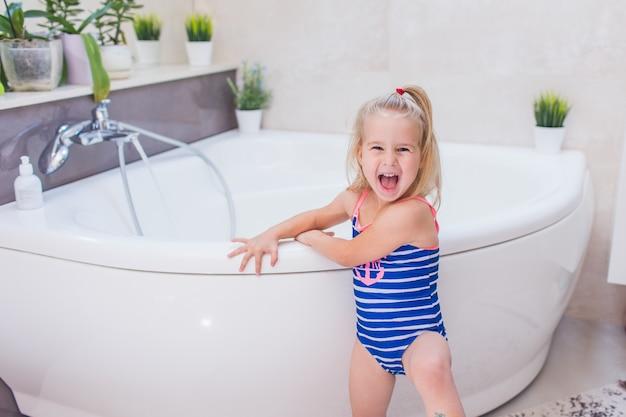 Szczęśliwa Mała Dziewczynka W Whetu Błękitnym Swimsuit Zostaje Blisko Wanny W łazience I Krzyczy Z Uśmiechem. Premium Zdjęcia