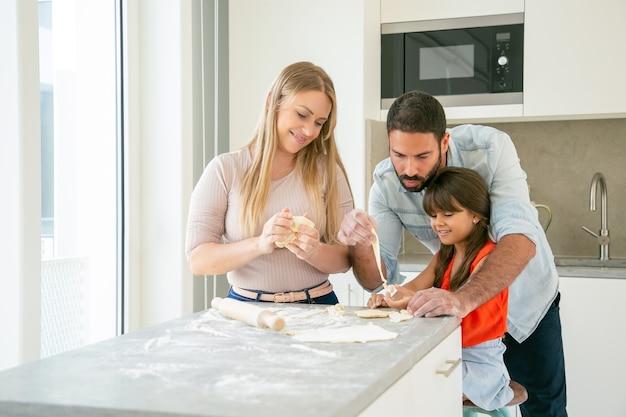Szczęśliwa Mama I Tata Uczą Córkę Wyrabiania Ciasta Przy Kuchennym Stole Z Mąką W Proszku. Darmowe Zdjęcia