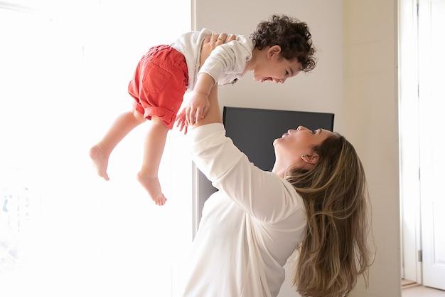 Szczęśliwa Mama Trzyma Podekscytowane Dziecko W Ramionach, Podnosząc Dziecko W Powietrzu. Widok Z Boku. Koncepcja Rodzicielstwa I Dzieciństwa Darmowe Zdjęcia