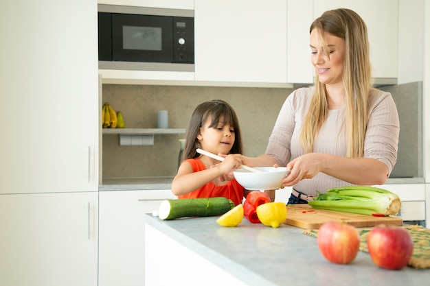 Szczęśliwa Mama Uczy śliczną Córkę Gotować Warzywa. Dziewczyna Pomaga Matce Podrzucić Sałatkę Na Blacie Kuchennym. Koncepcja Gotowania Rodziny Darmowe Zdjęcia