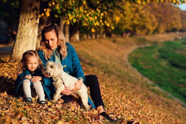 Szczęśliwa Mama Z Jej Dzieckiem Relaksuje Z Białym Teriera Psem Na Jesień Liściach. Premium Zdjęcia