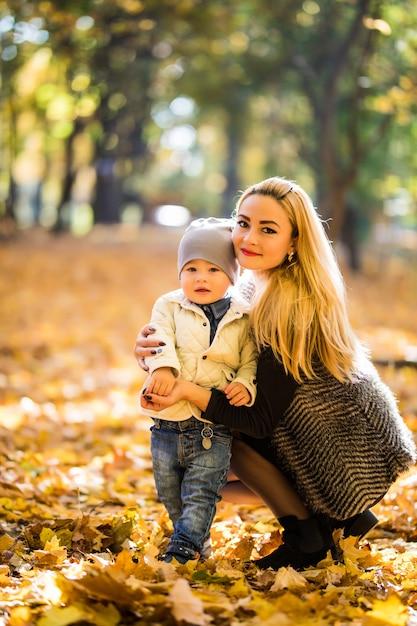Szczęśliwa Matka Bawi Się Z Dzieckiem W Parku Jesienią. Dziecko Uśmiecha Się Do Mamy Na Rękach Darmowe Zdjęcia