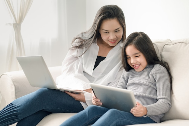 Szczęśliwa matka i córka z komputerem osobistym laptopu i pastylki Premium Zdjęcia