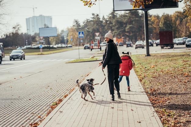 Szczęśliwa Matka I Jej Córka Chodzą Z Psem Na Ulicy. Darmowe Zdjęcia