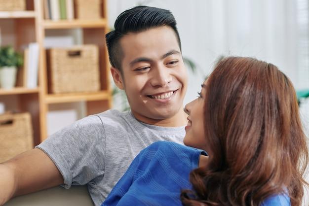 Szczęśliwa Młoda Azjatycka Kobieta Patrzeje Nad Ramieniem Przy Przystojnym Mężem W Domu Darmowe Zdjęcia