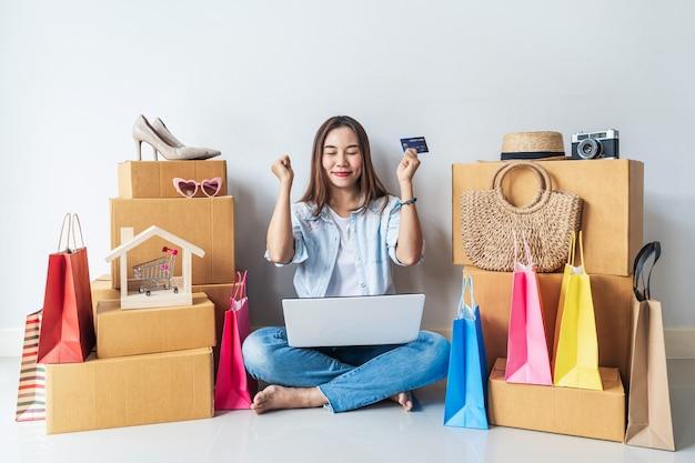 Szczęśliwa Młoda Azjatycka Kobieta Z Kolorową Torba Na Zakupy, Mod Rzeczami I Stertą Kartony W Domu Premium Zdjęcia