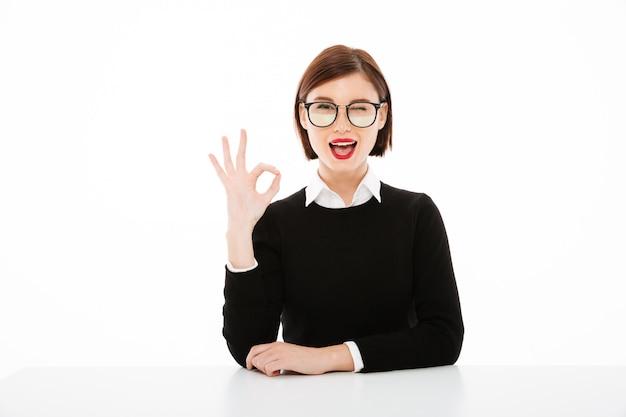 Szczęśliwa Młoda Biznesowa Dama Jest Ubranym Szkła Pokazuje Zadowalającego Gest. Darmowe Zdjęcia