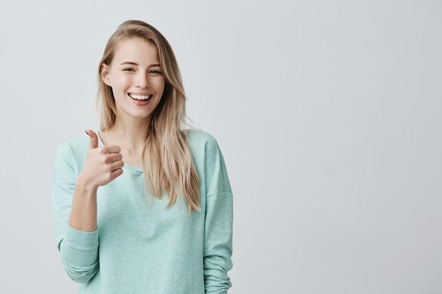 Szczęśliwa Młoda Caucasian Kobieta Jest Ubranym Błękitną Długą Rękaw Koszula Robi Kciukowi Up Podpisuje Darmowe Zdjęcia