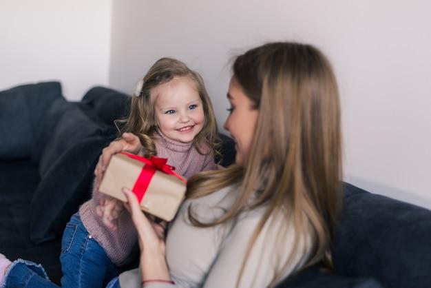 Szczęśliwa Młoda Dziewczyna Zaskakuje Jej Matki Z Prezentem W Domu W żywym Pokoju Darmowe Zdjęcia