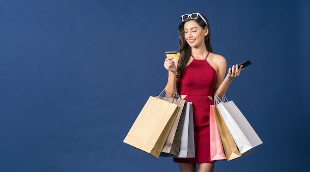 Szczęśliwa Młoda Kobieta Azji Patrząc Karty Kredytowej I Korzystania Z Telefonu Komórkowego Do Zakupów Online Na Niebieskim Tle Koloru Premium Zdjęcia
