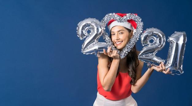 Szczęśliwa Młoda Kobieta Azji Trzymając Balony W Kolorze Srebrnym Do świętowania Wesołych świąt I Szczęśliwego Nowego Roku Na Niebieskim Tle Premium Zdjęcia