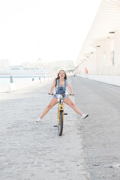 Szczęśliwa Młoda Kobieta Ma Zabawę Podczas Gdy Jadący Bicykl Darmowe Zdjęcia