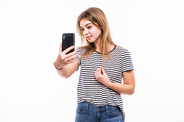 Szczęśliwa Młoda Kobieta Robi Zdjęcia Ona Przy Mądrze Telefonem Nad Biel ścianą Darmowe Zdjęcia