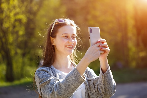 Szczęśliwa Młoda Kobieta Rozmawia Przez Połączenie Online W Smartfonie. Na Zewnątrz W Słoneczny Wiosenny Dzień W Parku Darmowe Zdjęcia