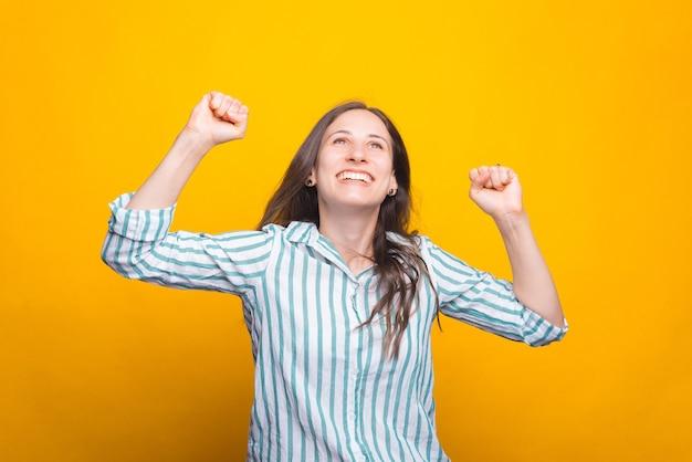 Szczęśliwa Młoda Kobieta Rozwesela Obiema Rękami Premium Zdjęcia