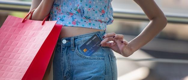 Szczęśliwa młoda kobieta trzyma kartę kredytową z kieszeni dżinsów z torby na zakupy, wydaje pieniądze z cieszyć się na zakupy. Premium Zdjęcia