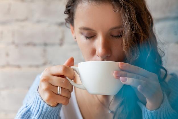 Szczęśliwa Młoda Kobieta W Ciepły Sweter Z Dzianiny, Trzymając Rękami Kubek Zdrowej Gorącej Niebieskiej Kawy Latte. Niebieska Kawa Latte Ze świeżymi Ziarnami Kawy I Herbatą Z Groszku Motylkowego Bluechai. Koncepcja Dobrego Samopoczucia. Premium Zdjęcia