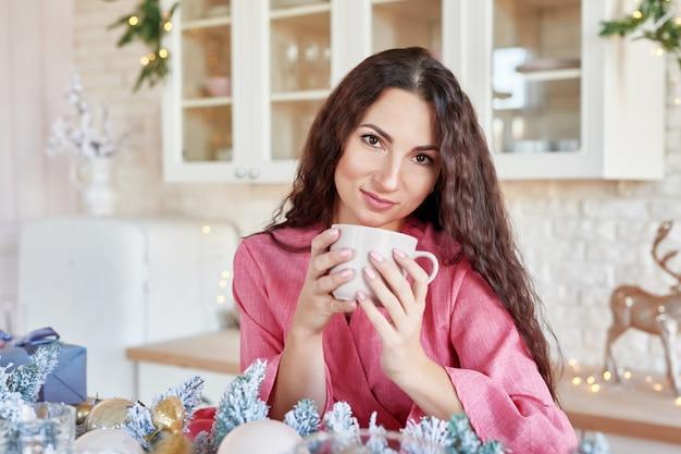 Szczęśliwa Młoda Kobieta W Różowej Sukience Z Filiżanką W Boże Narodzenie Urządzone Kuchnia. Piękna Brunetka Z Filiżanką Kakao W Kuchni Z świątecznym Wystrojem. Jasnobiałe Wnętrze Kuchni Na Boże Narodzenie. Kobieta W Domu Premium Zdjęcia