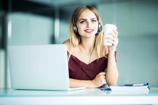 Szczęśliwa Młoda Kobieta W Słuchawkach W Call Center I Picia Kawy W Biurze. Darmowe Zdjęcia