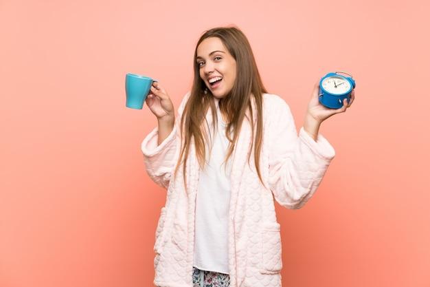 Szczęśliwa młoda kobieta w szlafroku na różowej ścianie, trzymając filiżankę kawy Premium Zdjęcia