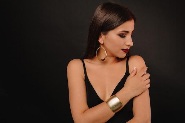 Szczęśliwa Młoda Kobieta Z Jasny Makijaż I Złota Biżuteria W Czarnej Sukni Pozowanie Darmowe Zdjęcia