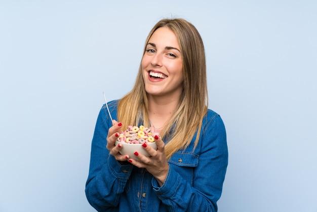 Szczęśliwa młoda kobieta z pucharem zbóż nad odosobnioną błękit ścianą Premium Zdjęcia