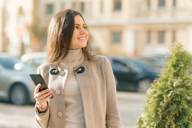 Szczęśliwa młoda kobieta z smartphone Premium Zdjęcia