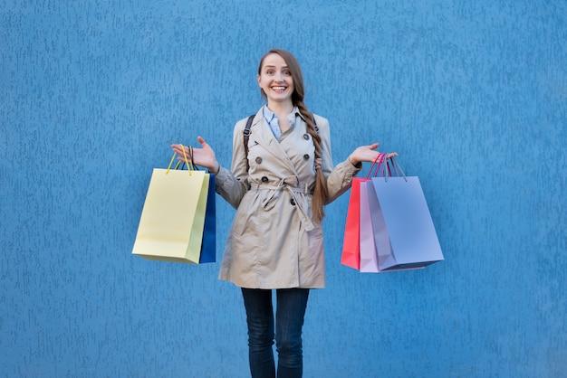 Szczęśliwa młoda kobieta zakupoholiczka z kolorowymi torbami. Premium Zdjęcia