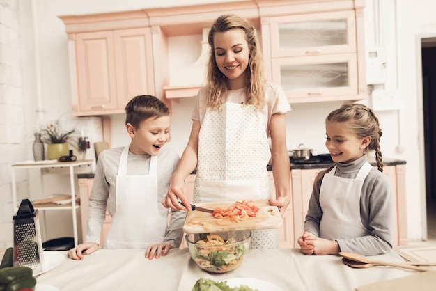 Szczęśliwa Młoda Mama I Dzieci Gotują Mix Domowej Roboty Sałatki. Premium Zdjęcia