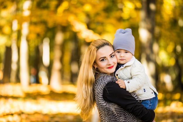 Szczęśliwa Młoda Matka Bawi Się Ze Swoim Małym Synkiem Na Słońce Ciepły Jesienny Lub Letni Dzień. Piękne światło Słońca W Ogrodzie Jabłkowym Lub W Parku. Szczęśliwa Rodzina Koncepcja Darmowe Zdjęcia