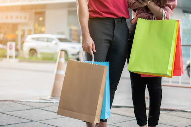 Szczęśliwa młoda para kupujących, chodzenie na ulicy handlowej w kierunku i trzymając w ręku kolorowe torby na zakupy. Premium Zdjęcia