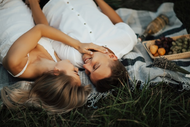 Szczęśliwa Młoda Para W Parku Odpoczywa Na Letnim Pikniku. Leżeli Na Kocu Na Zielonej Trawie, Patrząc Na Siebie I Uśmiechając Się. Premium Zdjęcia