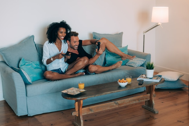 Szczęśliwa Młoda Para Zrelaksowała Się W Domu Na Kanapie, Grając W Gry Wideo Premium Zdjęcia