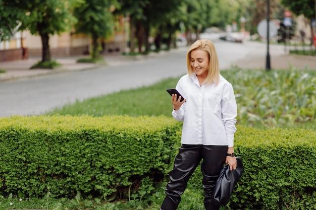 Szczęśliwa Młoda Piękna Kobieta Używa Jej Mądrze Telefonu Odprowadzenie Na Miasto Ulicie Darmowe Zdjęcia